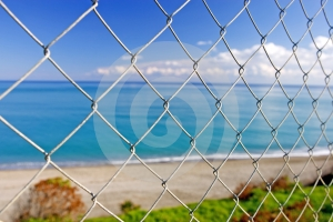 Beautiful Paradise Beach Seen Through Wires Of A Fence Royalty Free Stock Photos - Image: 575718