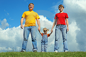 Happy family stand on green grass under sky Royalty Free Stock Photos