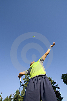 Man on Tennis Court Serving Tennis Ball Stock Photo