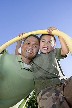 Father and Son Standing Under Pole - Vertical Stock Image
