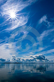 Rays of Sun on Blue Sky Reflecting in Lake Royalty Free Stock Image
