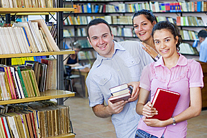 Three students in library Free Stock Photo