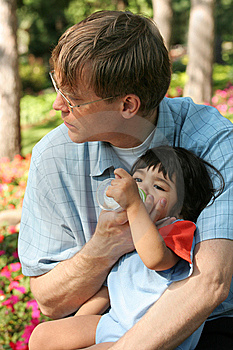 Father Feeding Baby A Bottle In The Park Royalty Free Stock Photo - Image: 6255695