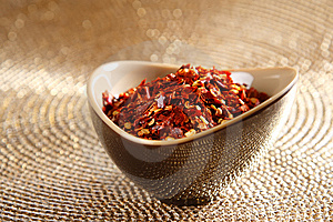Crushed Red Hot Chilli Pepper In Bowl On Golden Stock Photo - Image: 6568740