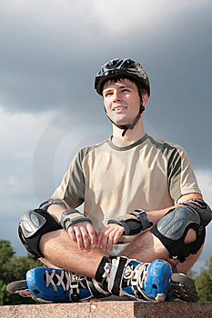 Boy On Rollerblades Sits With Crossed Legs In Yoga Stock Photos - Image: 6580503