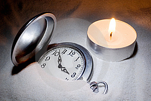 Watch Covered With Sand And A Candle Royalty Free Stock Photo - Image: 6595445
