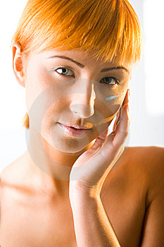 Young beauty putting face cream