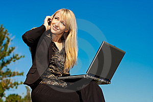 Woman With Laptop Talking On A Phone Stock Image - Image: 6778011