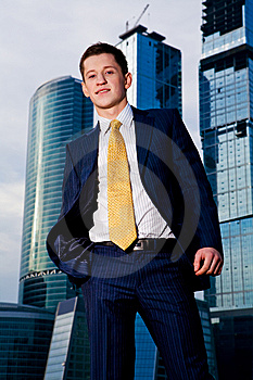 Friendly Businessman Standing Against Skyscraper Stock Photography - Image: 6900492