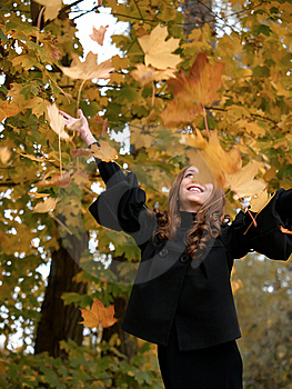 Youn Girl Throws Leaves Upwards In Forest. Royalty Free Stock Images - Image: 6905509