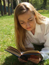 Woman reading on the grass Stock Images