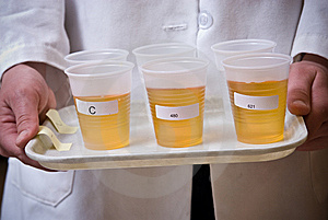 Amber Liquid In Plastic Cups On Plate Stock Image - Image: 7747461