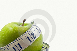 Green Apple Wrapped By A Measuring Tape Stock Photography - Image: 7777052