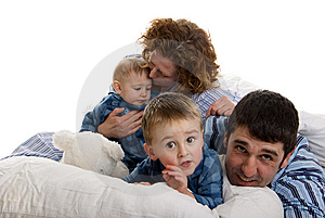 Family of four relaxes in bed Royalty Free Stock Images
