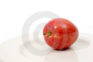 Red apple on white plate Royalty Free Stock Photography