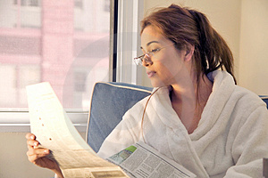 Stock Image - Brunette reading the morning papers