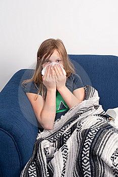 Una niña que está enferma con un resfriado o la gripe.