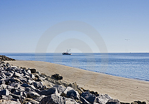 Shrimp Boat Past Rocky Beach Stock Images - Image: 8540334