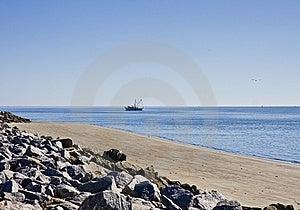 Shrimp Boat Past Rocky Beach Stock Images - Image: 8540334