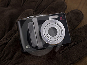 Point & Shoot Digital Camera On Leather Gloves Stock Images - Image: 8569874