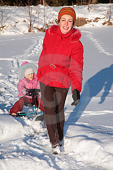 Mother Pulls Daughter On Snow Scooter Stock Photo - Image: 8631520
