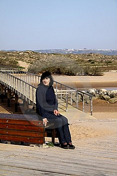 Woman Sitting Next To A Bridge Royalty Free Stock Image - Image: 8641596