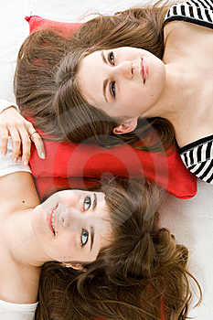 Two Girls Lying On Red Pillow Stock Image - Image: 8735531