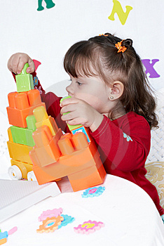 Little Girl Plays A Colorful Cubes Royalty Free Stock Image - Image: 8992846