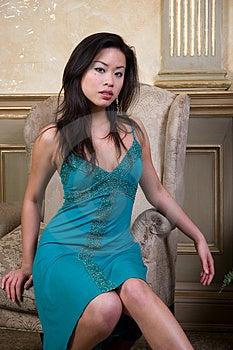 Ázijské model sedí vpred v stoličke, oblečenú zelenú večerné šaty.