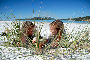 Two Young Girls Hiding Behind Grass On Beach Stock Image - Image: 9222241