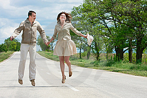 Couple Jumping On Rural Road Royalty Free Stock Image - Image: 9544616