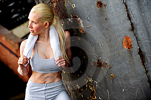 Blond Female Jogger Leaning Against A Wall Royalty Free Stock Photography - Image: 9622827