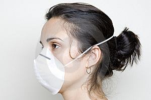 Young Woman Putting On A Mask Against Swine Flu Stock Photography - Image: 9630712