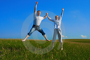 Couple jumping in field Royalty Free Stock Images