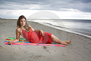 Attractive Girl Laying On A Towel With Red Dress Stock Photos - Image: 9804793