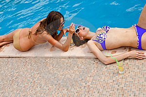 Girl Giving A Drink To The Other On The Pool Royalty Free Stock Image - Image: 9967036