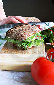 Dividing healthy rye bread sandwich in half Royalty Free Stock Photography