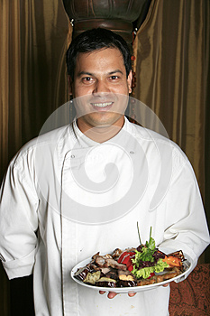 Cook Takes Off The Fried Meat And Green-stuffs Stock Image - Image: 9990611